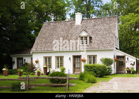 Old (circa 1886) white with beige and brown trim Canadiana cottage style home facade in summer, Quebec, Canada - Stock Photo