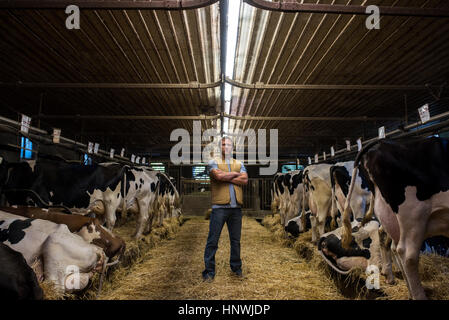 Portrait of farmer in cow shed - Stock Photo