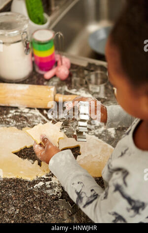 Girl cutting cookie dough with cookie cutters - Stock Photo