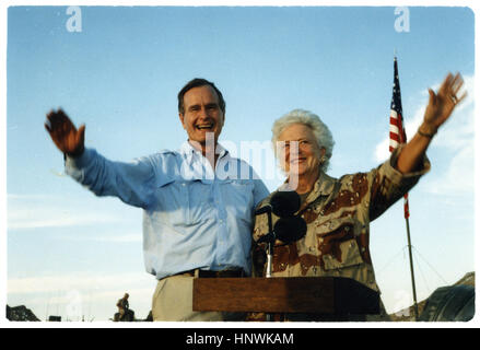 President George Bush and First Lady Barbara Bush wave as they stand in the back of a vehicle during a visit to - Stock Photo
