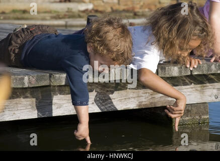 Model release, Zwei Kinder liegen auf Holzsteg und greifen in Teichwasser - children on wood stage - Stock Photo