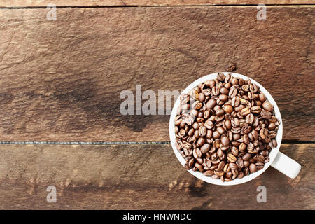 Overhead shot of a white cup filled with whole fresh coffee beans over a wood table top. Flat lay top view style. - Stock Photo