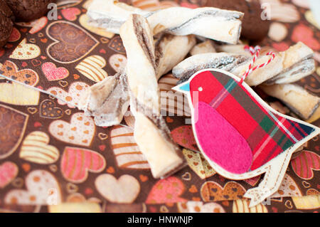 Red toy bird and cookies on dark napkin with image of heartsclose up. Selective focus. - Stock Photo