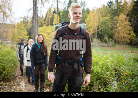 Smiling Man With Friends Hiking On Forest Trail - Stock Photo