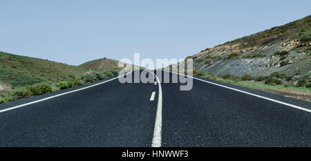 view of a lonely road in a rural landscape with no traffic - Stock Photo