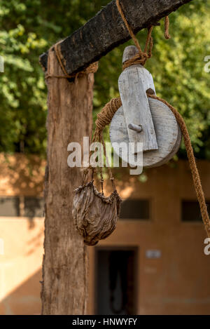 Old pulley and leather water bucket.  Wooden pulley with natural fibre rope holding a leather bucket to collect - Stock Photo