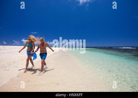 Mature couple walking along beach, holding hands, Ile aux Cerfs, Mauritius - Stock Photo