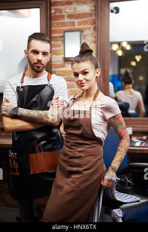 Hairdressers in barber shop looking at camera smiling - Stock Photo