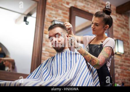 Hairdresser cutting customer's hair - Stock Photo