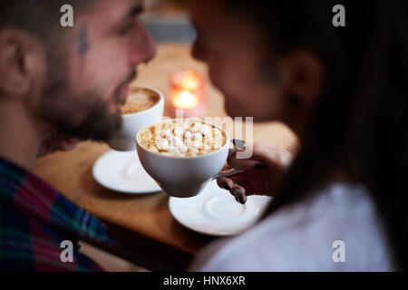 Couple in coffee shop face to face smiling - Stock Photo