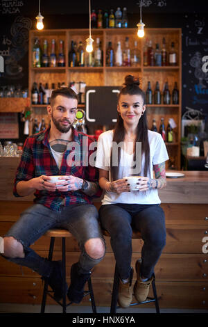 Couple sitting side by side on stools in cafe looking at camera smiling - Stock Photo