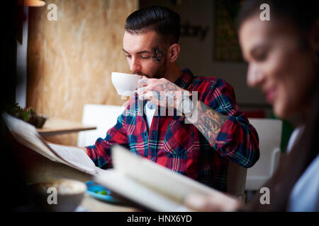 Couple drinking coffee reading newspapers - Stock Photo