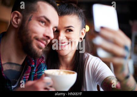 Couple in cafe taking selfie - Stock Photo