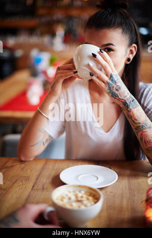 Tattooed woman in cafe drinking coffee looking at camera - Stock Photo