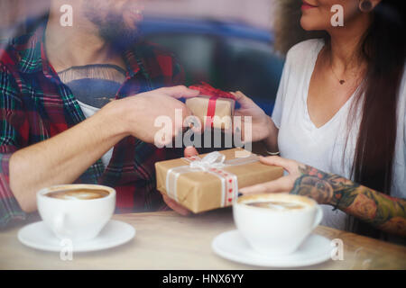 View through window of couple in coffee shop exchanging gifts - Stock Photo