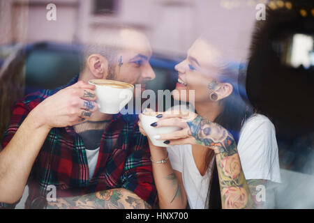 View through window of couple in coffee shop face to face smiling - Stock Photo