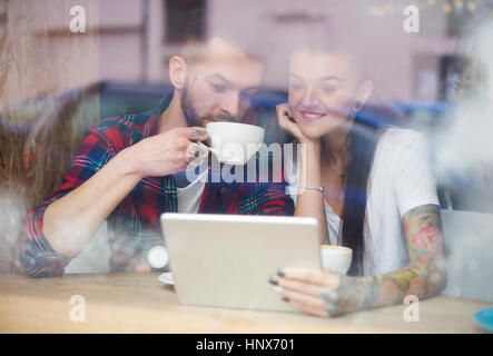 View through window of couple in coffee shop using digital tablet - Stock Photo