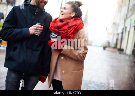 Couple with disposable cups holding hands - Stock Photo