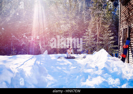 Woman practicing yoga, kneeling on yoga mat by log cabin in snow,  Austria - Stock Photo