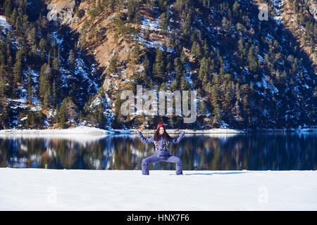 Woman in winter clothes practicing yoga pose on snowy lakeside, Austria - Stock Photo