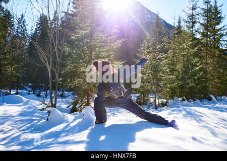 Woman in winter clothes practicing side angle yoga pose in snowy forest, Austria - Stock Photo