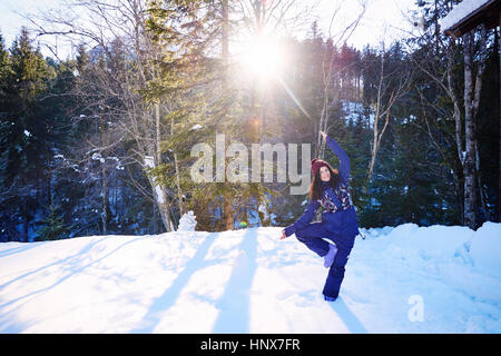 Woman in winter clothes practicing tree yoga pose in snow by forest, Austria - Stock Photo