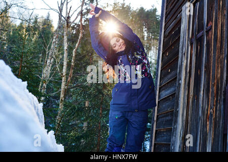 Woman in winter clothes practicing half moon yoga pose in snow by log cabin, Austria - Stock Photo