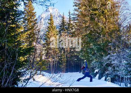 Woman in winter clothes practicing warrior yoga pose in snowy forest, Austria - Stock Photo