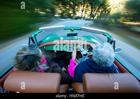 Rear view of senior couple speeding on rural road driving vintage convertible, Majorca, Spain - Stock Photo