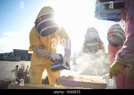 Male and female beekeepers using bee smoker on city rooftop - Stock Photo