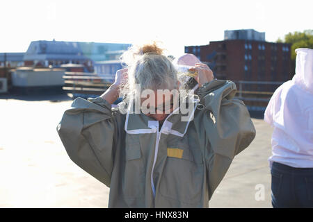 Female beekeeper putting on protective clothes on city rooftop - Stock Photo