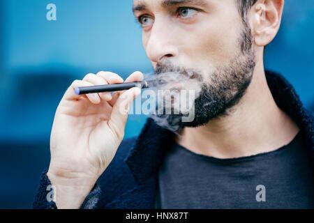 Portrait of man smoking an electronic cigarette - Stock Photo