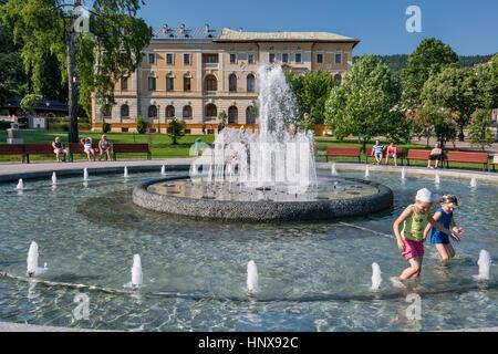 Children at fountain, Stary Dom Zdrojowy spa house in Krynica Zdroj spa resort, Beskid Sadecki region, Western Carpathians, - Stock Photo