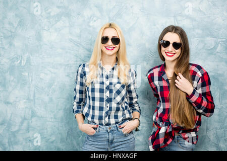 Portrait of two female friends in checkered shirts, jeans and sunglasses on the blue painted wall background - Stock Photo
