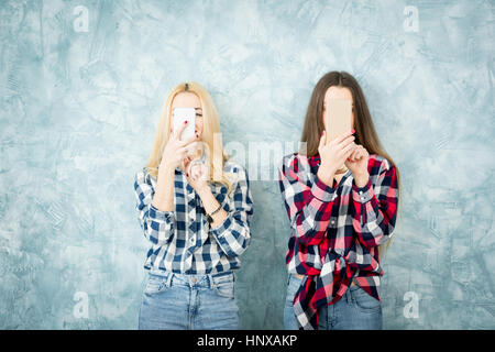 Female friends in checkered shirts using smart phones on the blue wall background - Stock Photo