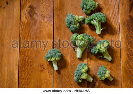 fresh organic green broccoli on a wooden background - Stock Photo