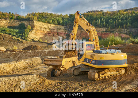Quarrying sand with a digger and tipper in a quarry - Stock Photo