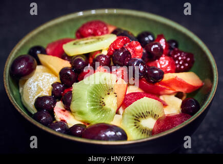 A green bowl of mixed fruit salad with blueberry kiwi tangerine and mango slices - Stock Photo