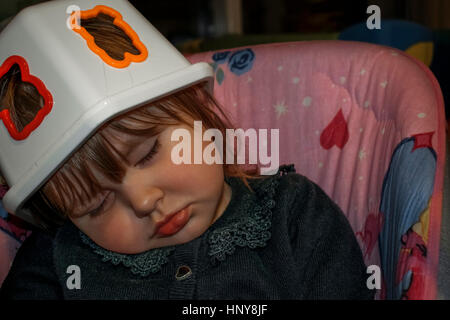 Blond baby girl asleep on a baby swing with a plastic toy box on her head as a hat. She wears a black lace blouse - Stock Photo