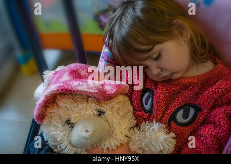 Blond baby girl sitting on baby swing, asleep holding a furry teddy bear. She wears a pink fur sweater. - Stock Photo