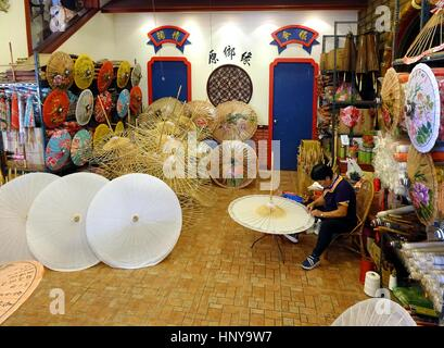 KAOHSIUNG, TAIWAN -- JULY 24, 2016: A female craftsperson makes oil-paper umbrellas, which is a traditional art - Stock Photo