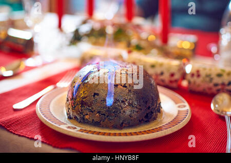 Christmas pudding flaming with brandy - Stock Photo
