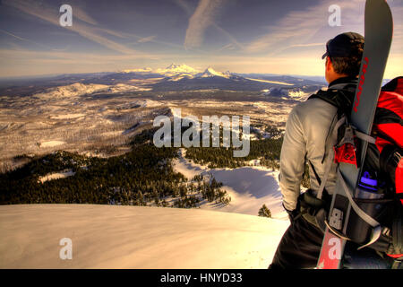 Backcountry Skier Overlooking the Horizon from the Summit of Three Fingered Jack Mountain Outside Sisters Oregon - Stock Photo