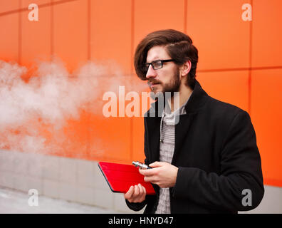 Young hipster man with a beard and glasses smokes an electronic cigarette. He holds a tablet pc. - Stock Photo