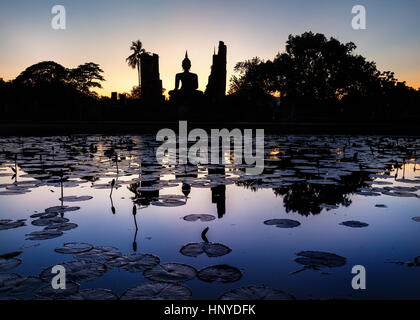 Beautiful scenery of Wat Mahathat Temple in Sukhothai Historical Park with Buddha statue silhouette and reflections - Stock Photo