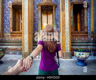 Woman in hat and purple t-shirt leading man by hand to the Wat Phra Kaew famous temple in Bangkok, Thailand - Stock Photo