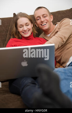 Model release , Junges Paar sitzt mit Laptop auf der Couch - couple using laptop on couch - Stock Photo