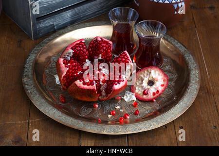 ripe pomegranate on copper plate on a dark background, close view - Stock Photo