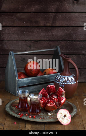 Ripe pomegranate fruit with pomegranate juice on copper plate and fruit box and jug on wooden vintage table. - Stock Photo
