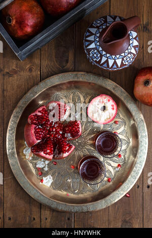 Ripe pomegranates with juice on copper plate on wooden background, top view - Stock Photo